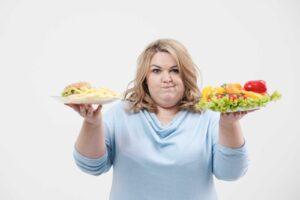 Adipöse Frau mit ungesundem und gesundem Essen