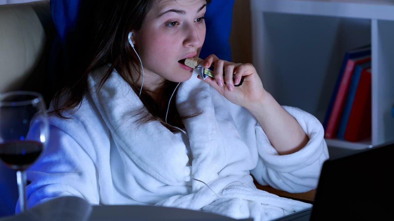 junge Frau ist einen Schokoriegel am Laptop
